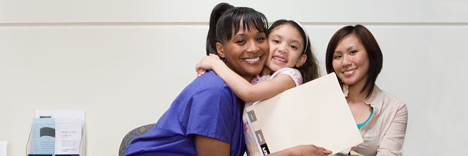 Student nurse embracing in a hug with a little girl and mother sitting next to her.