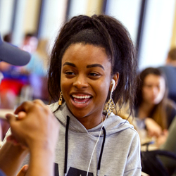 A students smiles inside a dining hall.